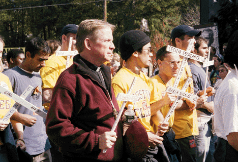 Fr. Don MacMillan, S.J., walks with Boston College students taking part in the nonviolent vigil at the gates of Ft. Benning on the Sunday following the Ignatian Family Teach-In for Justice.  [Year Unknown]